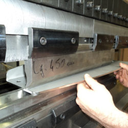 Métallurgiste qui pli un morceau d'acier dans l'atelier d'Atlantique Conception